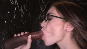 Girl with glasses is handling a cock in the glory hole naked